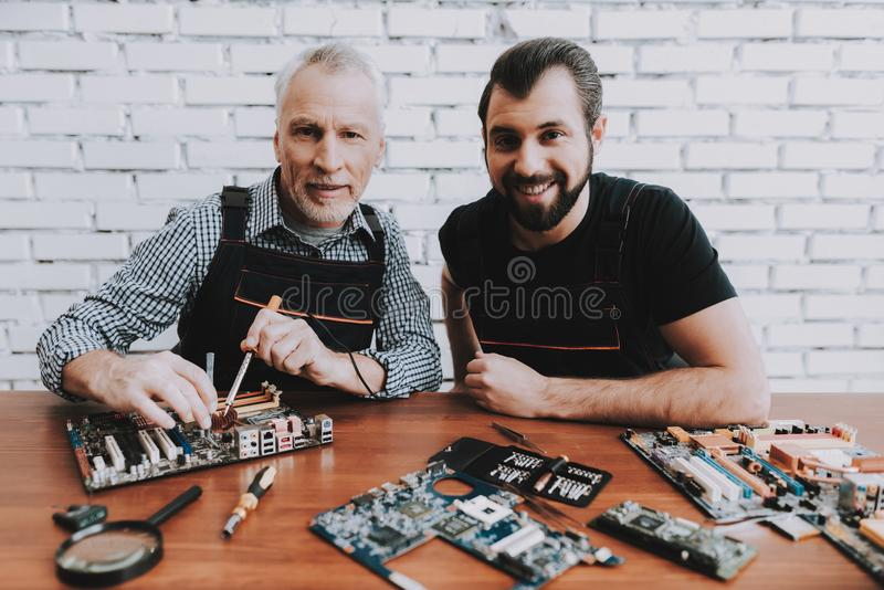 Two Men Repairing Hardware Equipment from PC. Repair Shop. Worker with Tools. Computer Hardware. Young and Old Workers. Soldering Iron. Digital Device. Laptop stock photography