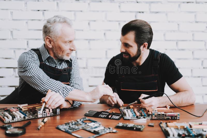 Two Men Repairing Hardware Equipment from PC. Repair Shop. Worker with Tools. Computer Hardware. Young and Old Workers. Soldering Iron. Digital Device. Laptop royalty free stock images
