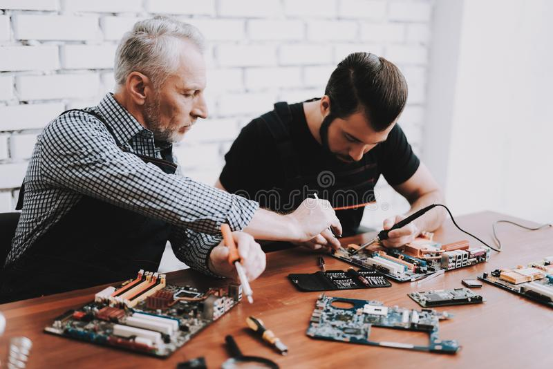 Two Men Repairing Hardware Equipment from PC. Repair Shop. Worker with Tools. Computer Hardware. Young and Old Workers. Soldering Iron. Digital Device. Laptop stock photos