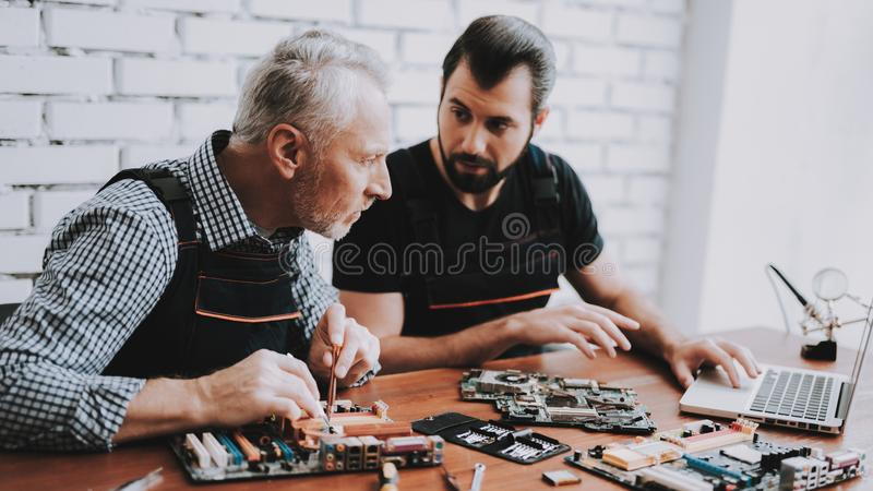 Two Men Repairing Hardware Equipment from PC. Repair Shop. Worker with Tools. Computer Hardware. Young and Old Workers. Modern Devices. Digital Device. Laptop stock image