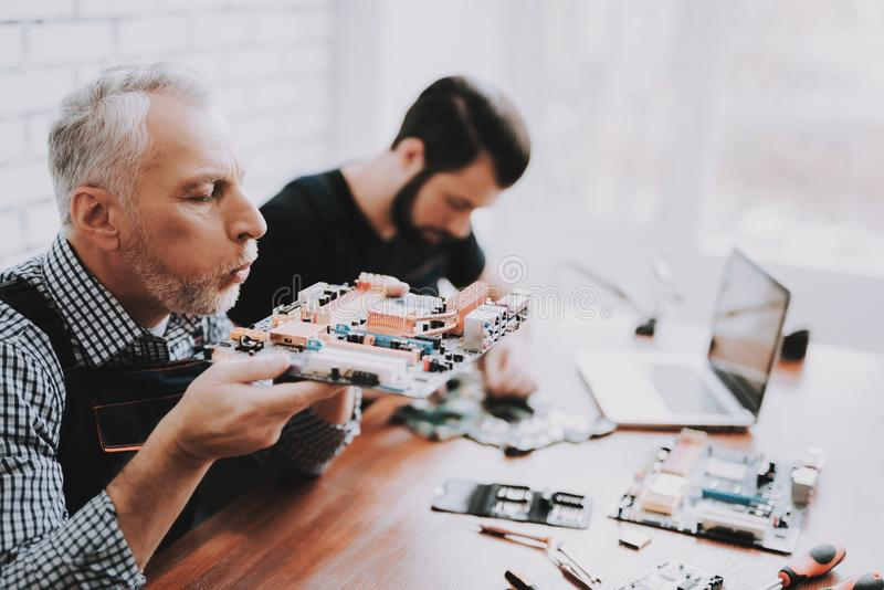 Two Men Repairing Hardware Equipment from PC. Repair Shop. Worker with Tools. Computer Hardware. Young and Old Workers. Modern Devices. Digital Device. Laptop royalty free stock images