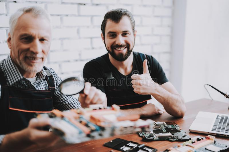 Two Men Repairing Hardware Equipment from PC. Repair Shop. Worker with Tools. Computer Hardware. Young and Old Workers. Modern Devices. Digital Device. Laptop royalty free stock image
