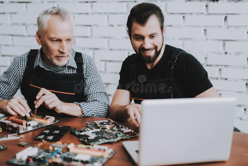 Two Men Repairing Hardware Equipment from PC. royalty free stock photos