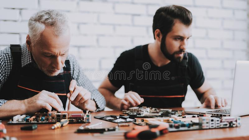 Two Men Repairing Hardware Equipment from PC. Repair Shop. Worker with Tools. Computer Hardware. Young and Old Workers. Modern Devices. Digital Device. Laptop royalty free stock photography