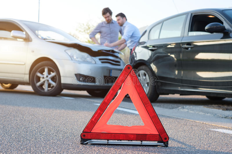 Two men reporting a car crash for insurance claim. Two men reporting a car crash for the insurance claim royalty free stock image