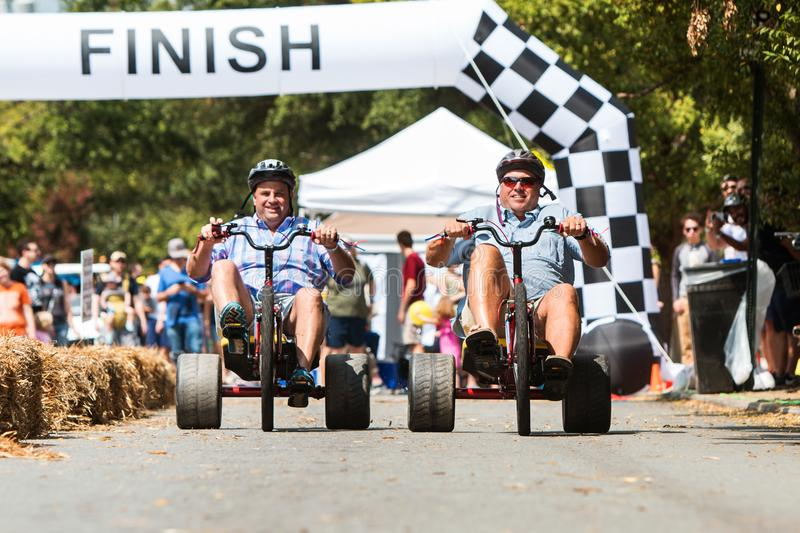 Two Men Riding Adult Big Wheels Race At Atlanta Festival stock photo