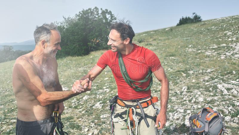 Two man rock climbers climbed on the cliff. Two men rock climbers climbed on the cliff. happy climbers on the top of the mountain. friends congratulate each stock photography
