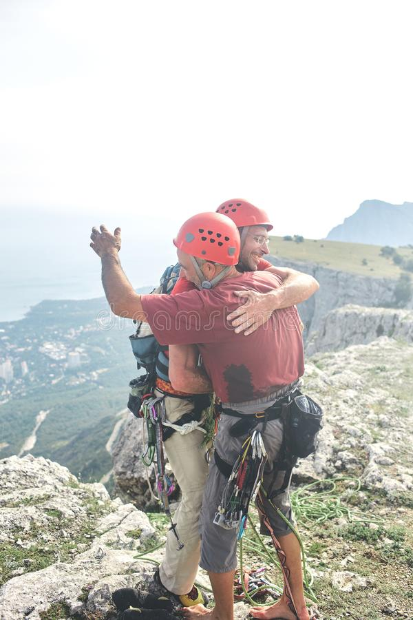 Two man rock climbers climbed on the cliff. Two men rock climbers climbed on the cliff. happy climbers on the top of the mountain. friends hug and congratulate stock image