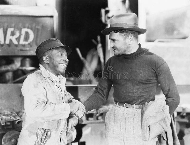 Two men shaking hands with each other. (All persons depicted are no longer living and no estate exists. Supplier grants that there will be no model release stock photography