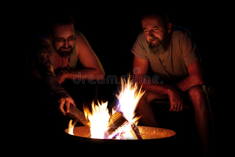 Two men sitting on a campfire at night, barbecue and camping at. A fireplace, black background stock image
