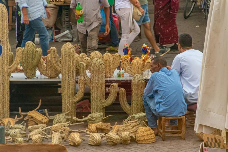 Two men sitting in a decorative straw cactus stand in Marrakech. Morocco, in October 2019 royalty free stock photo