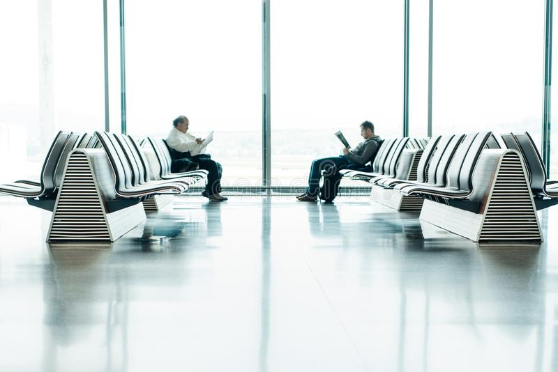 Two Men Sitting in Front of Each Other on White Gang Chairs in Airport Waiting Area royalty free stock photography