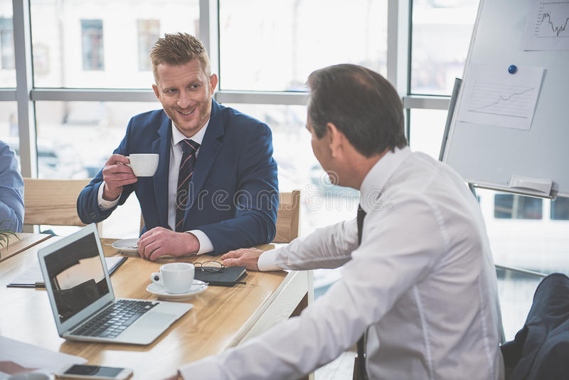 Two men are smiling at work stock photography
