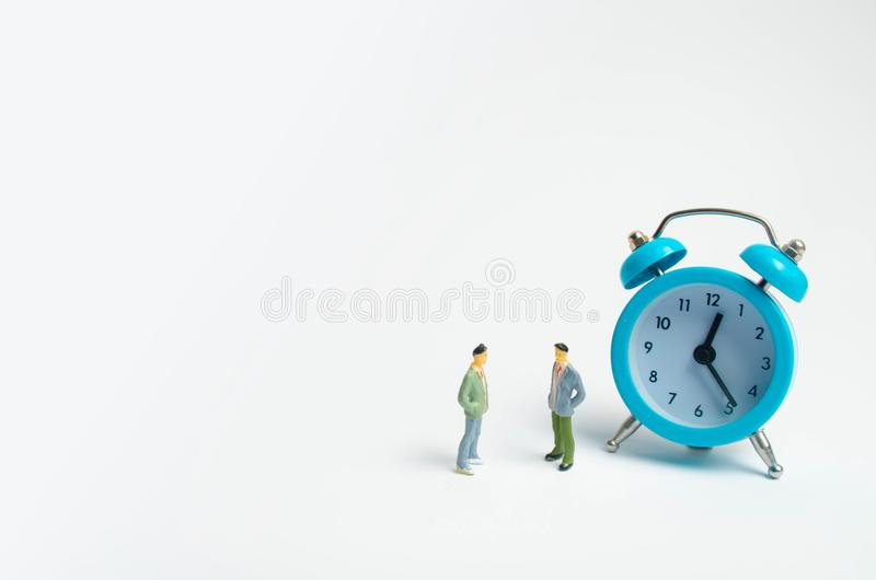 Two men stand near the blue alarm clock and talk. The concept of waiting for a meeting, a date. Punctuality. The cost of hourly wo. Rk of a specialist, business royalty free stock photos