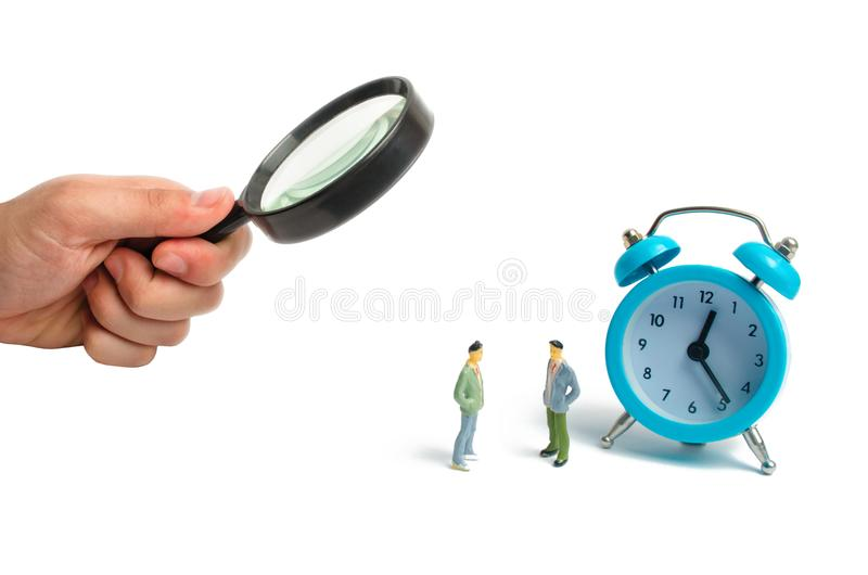 Two men stand near the blue alarm clock and talk. The concept of waiting for a meeting, a date. Punctuality. The cost of hourly wo. Rk of a specialist, business stock photos