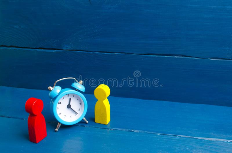 Two men stand near the blue alarm clock and talk. The concept of waiting for a meeting, a date. Punctuality. The cost of hourly stock photos