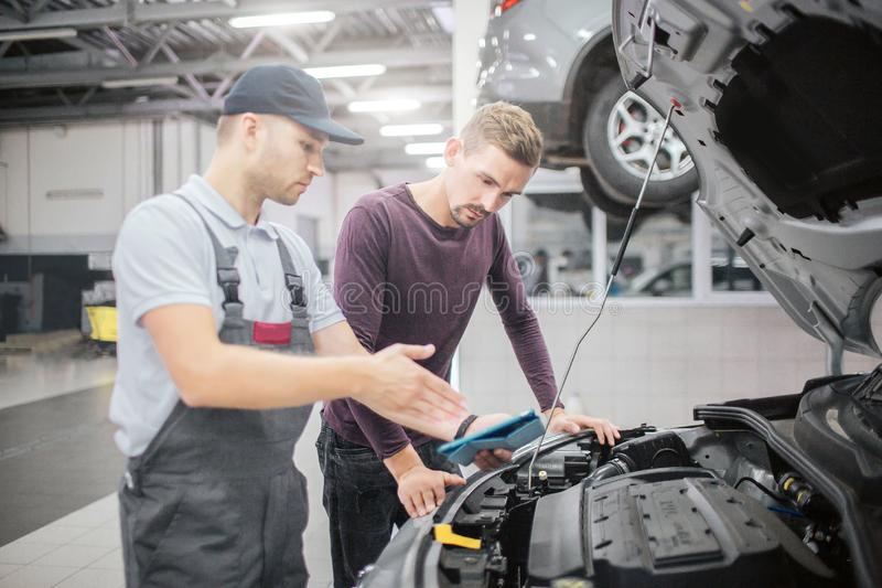 Two men stand at opened front part of car body. Worker point on it. They have conversation. Bearded young man listening royalty free stock photos