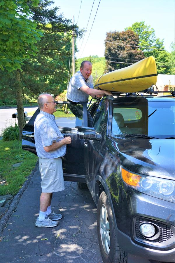 Two men strap an old yellow kayak to a car roof stock photo