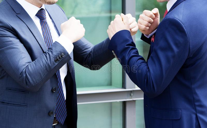 Two men in suit standing outside and fighting with their fists stock photos