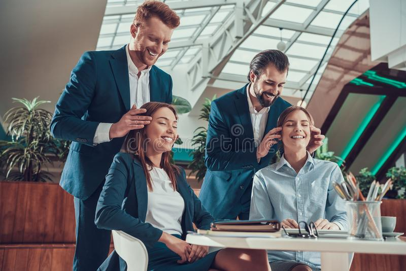 Two men massage heads of two women in office. Two men in suits massage heads of two women in office stock photo