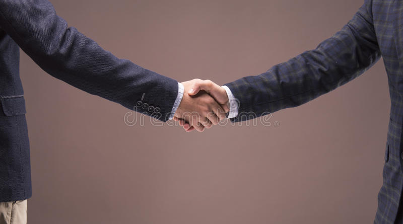 Two men in suits shake hands royalty free stock image