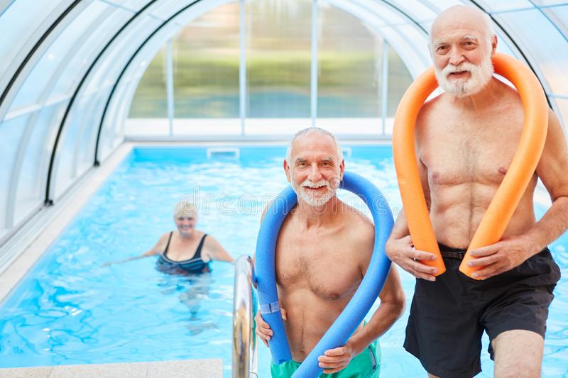 Two men in the swimming pool with swimming noodle royalty free stock image