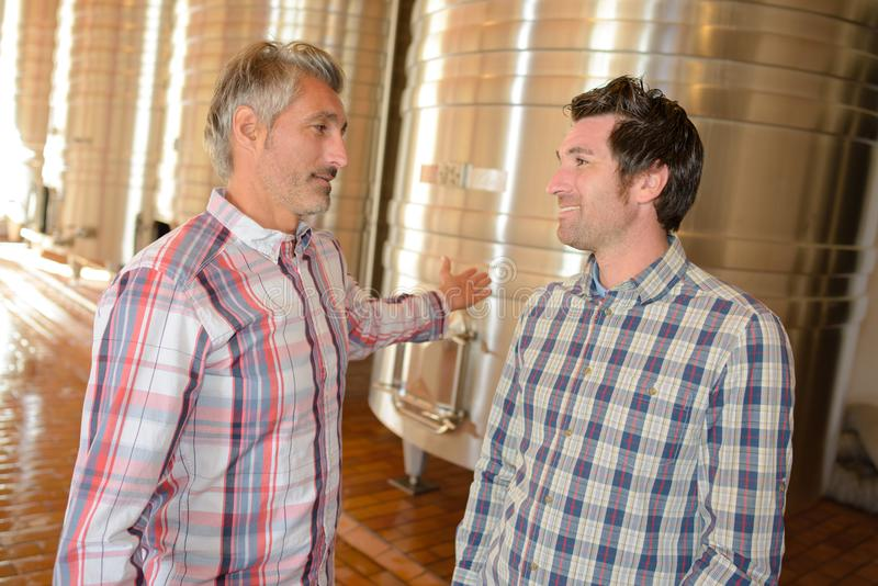 Two men talking next to wine vats stock photo