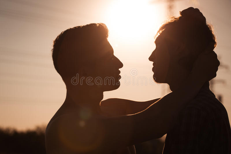 Two men about to kiss. Silhouette of two men about to kiss royalty free stock image