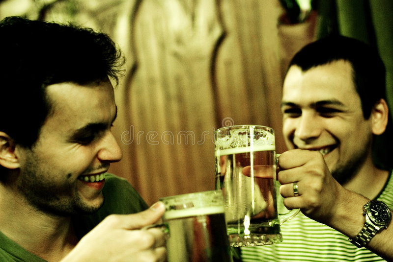 Two men toasting. Cheers, two young adult men toasting with their beer mugs in a pub. Entertaining. Image has noise royalty free stock images