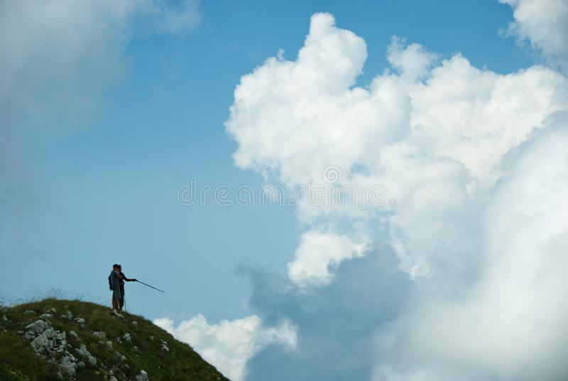 Two men on the top of the mountain. Men pointing with trekking poles. Two tourists on the edge of the cliff stock photography