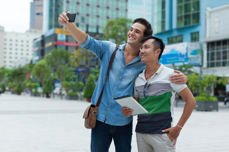 Two men tourists taking selfie photo smile, asian. Mix race friends guys outdoor city street royalty free stock image