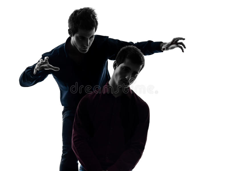 Two men twin brother friends domination concept silhouette. Two young men domination concept shadow white background stock image