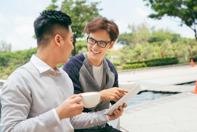 Two Men Using Tablet Computer Internet, Asian  Friends Guys Sitting at Cafe Natural Light royalty free stock image