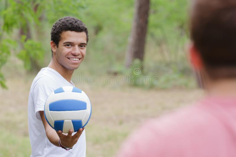 Two men and volleyball outdoors stock photo