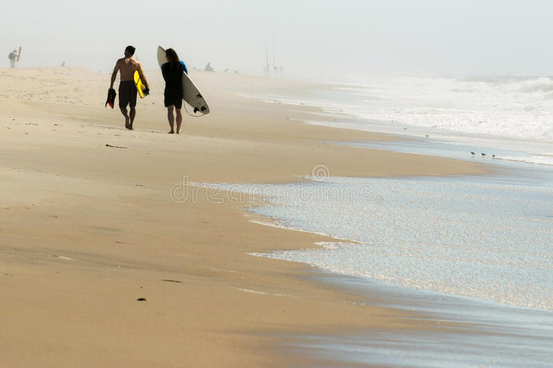 Two men walking down the beach with surfboards. 2 men with surfboards walk down the beach on a hazy morning stock image