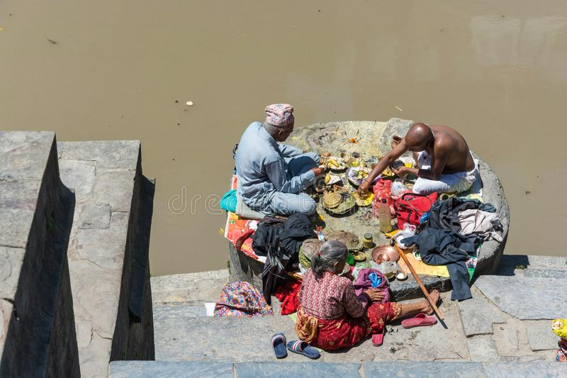 Two men and a woman eating on the banks of the Bagmati river in. Kathmandu, Nepal – 13.04.2018 Two men and a woman eating on the banks of the Bagmati royalty free stock photos