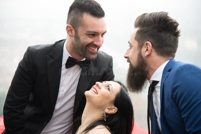 Two men and a woman in love triangle, smiling resumed in the foreground. Friendship love jealousy adultery polygamy concept. Love triangle stock image
