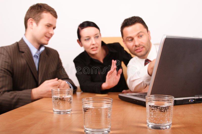 Two men and woman working on project with laptop. Glasses of sparkling water in focus at the front royalty free stock image