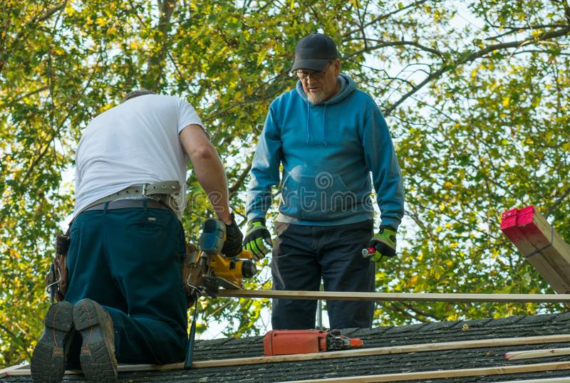 Two men working on the roof stock photography
