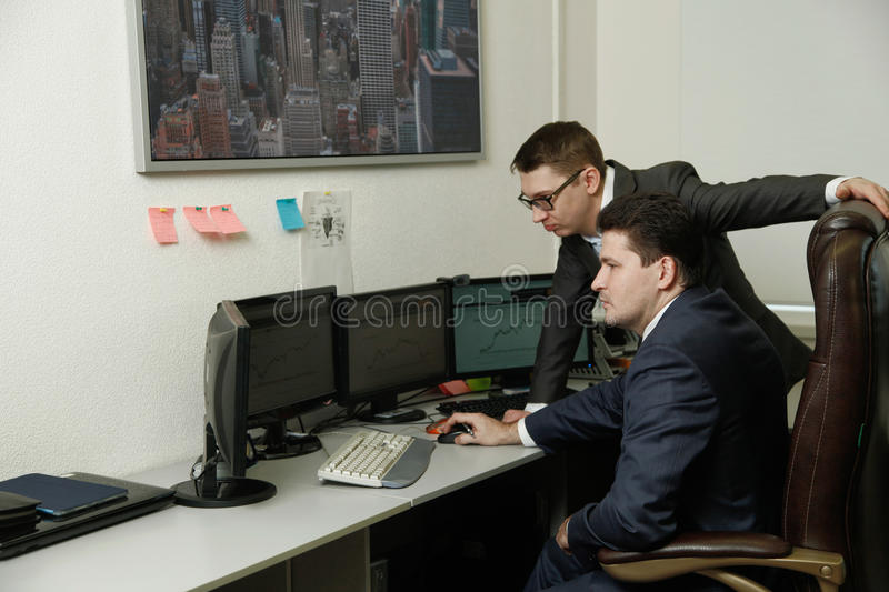 Two men working together for the computers in the office engaged in trading stock image