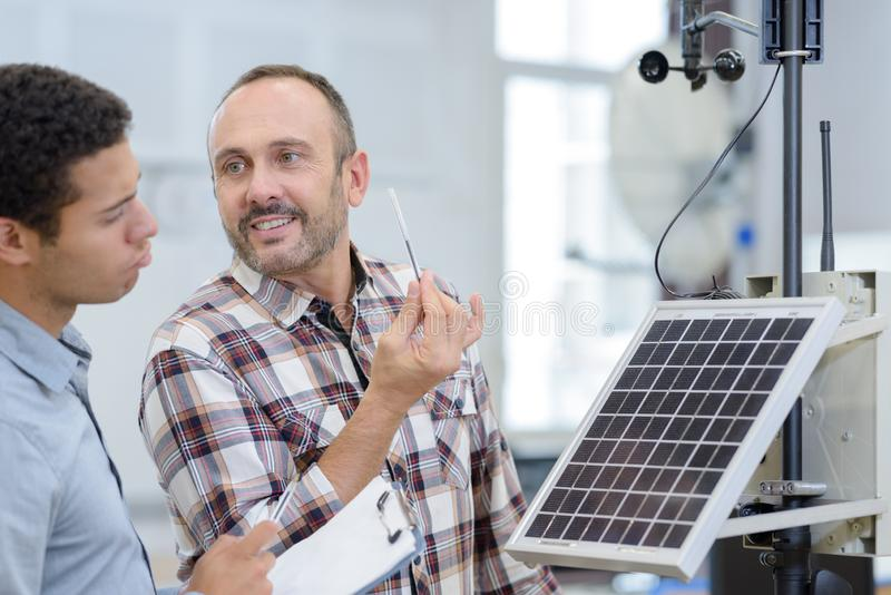 Two men in workshop. Two men in a workshop royalty free stock photography