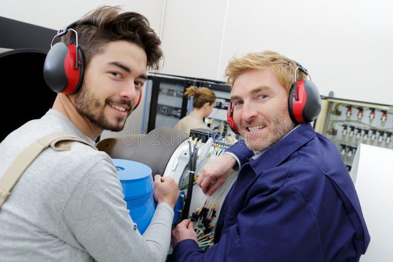 Two men in workwear in workshop stock photo