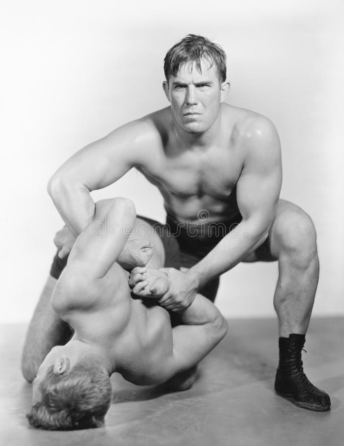 Two men wrestling with each other stock photo