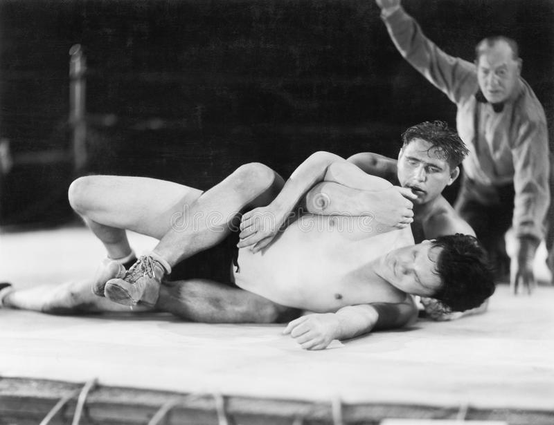 Two men wrestling with a referee in the background stock photography