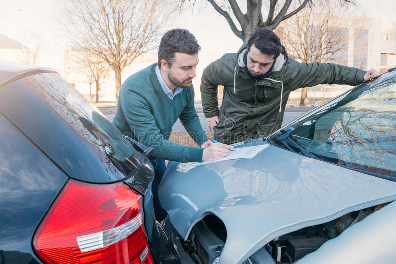 Two men writing a car insurance claim. After a car crash royalty free stock photography