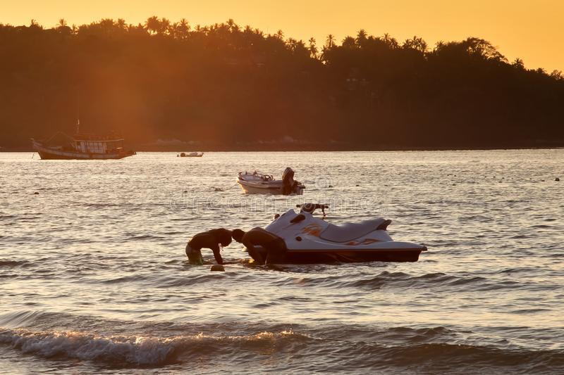 Two mens at sunset pull hydrocycle out of the water. Summer vacation. Water bike loaded onto a trailer.  stock images