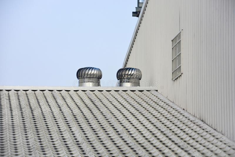 Two of metal air ventilators or air blower cooling on the metal sheet factory roof spinning take cool wind into the building stock photography