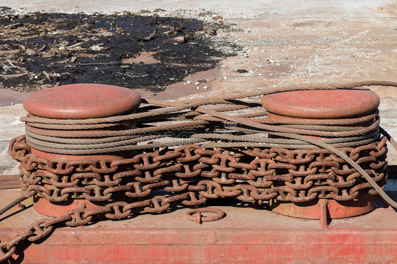 Two metal bollards with rusty chains and cables stock photos