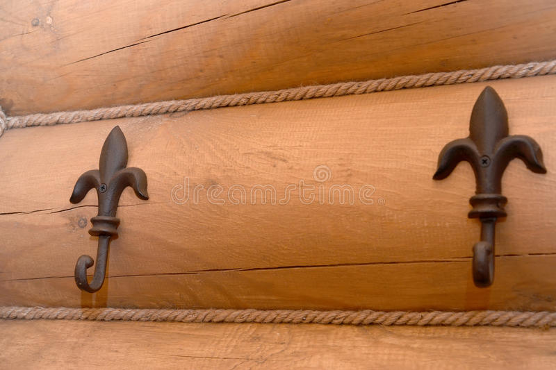 Two metal hooks hangers in the form of lilies on a timbered wall royalty free stock photos
