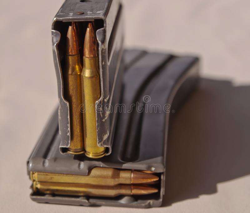 Two metal rifle magazines. One stacked upon the other, loaded with .223 caliber bullets stock photos